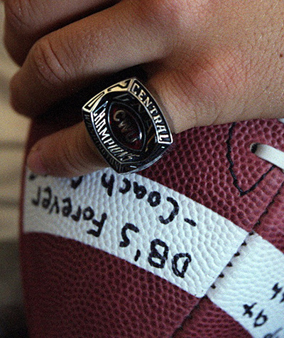 Holding a signed football and wearing a championship ring